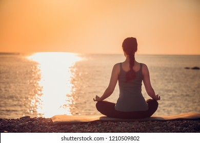 Woman practicing yoga lotos position. Sunset over sea in the background.