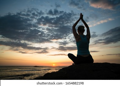 Woman practicing yoga in Lotus position on the ocean coast at twilight.