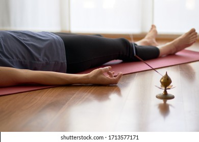 woman practicing yoga, lying in yoga nidra pose, exercise in Shavasana, exercises, work, rest after practice, female hand. Healthy lifestyle concept