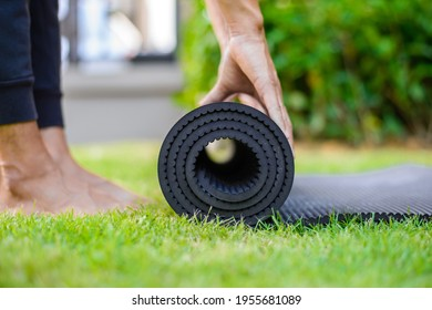 Woman practicing yoga and meditating outdoors. Girl preparing material for practice class in garden. Female happiness and yoga concept. During the quarantine due to the spread of the coronavirus.