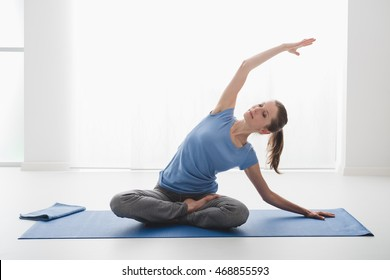 Woman practicing yoga and meditation at home on the floor, she is sitting with legs crossed and bending on a side