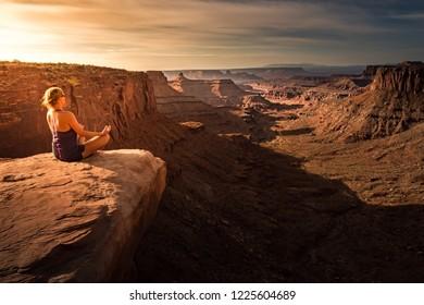 Woman practicing yoga meditation at Sunrise. Beautiful Canyonland Landscape
