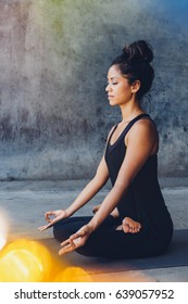 Woman practicing yoga and meditation in a urban background