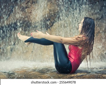 Woman practicing yoga near waterfall. Boat Pose. Navasana