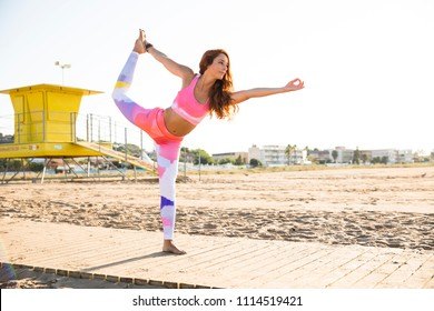 Woman practicing yoga on the beach in Barcelona