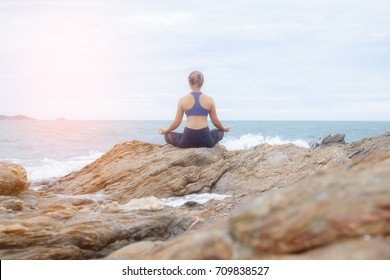 The woman practicing yoga on the beach at sunset.