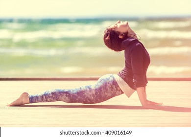 woman practicing yoga on the coast of sea, sunny day