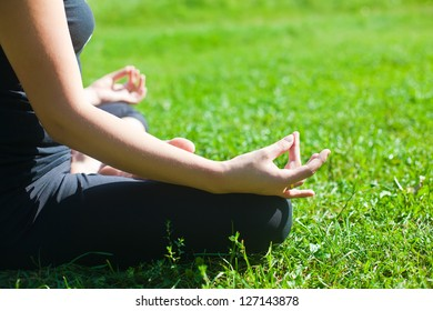 woman practicing yoga on a grass