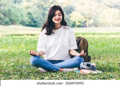 Woman practicing yoga on green grass background