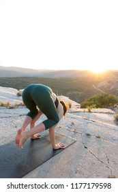 Woman practicing yoga on nature mountain top during sunset