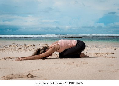 Woman practicing yoga on ocean beach - child's pose
