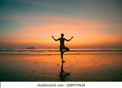 An woman practicing yoga on the ocean side, the silhouette of awesome sunset.
