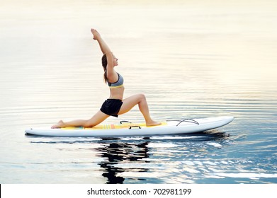 Woman practicing yoga  on the paddle board in the morning