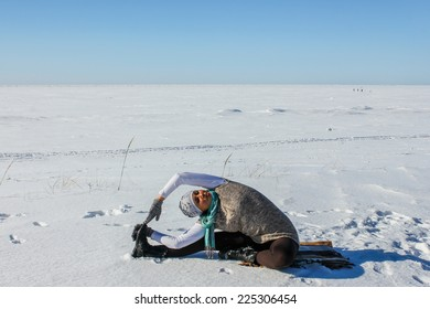 Woman practicing yoga on snow