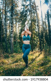 The woman practicing yoga outdoors  in a green sportswear. Eagle Pose, Garudasana. Hatha yoga. Around the green forest and sunbeams. Fit sportive girl doing advanced pilates, fitness. Full length