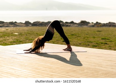 Woman practicing yoga in park. ADHO MUKHA SVANASANA / DOWNWARD FACING DOG
