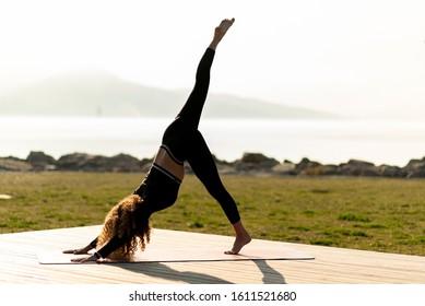 Woman practicing yoga in park. Downward Facing Dog Split (Eka Pada Adho Mukha Svanasana)