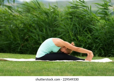 Woman practicing yoga in the park Seated Forward Bend