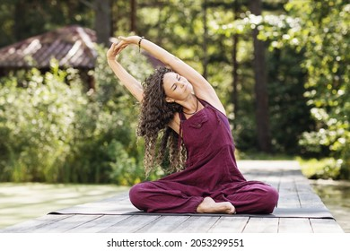 A woman practicing yoga, performing a lateral bending exercise in siddhasana, sits on a mat in a park on a sunny morning on a wooden bridge near a pond