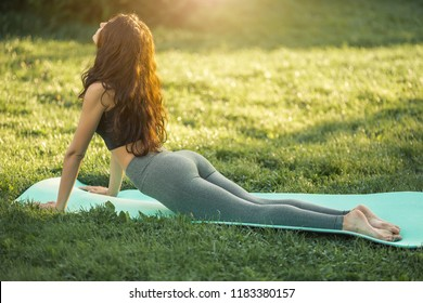Woman practicing yoga performing yoga-asanas outdoors. Young attractive slim fitness girl in bodysuit relaxing and doing exercises, laying and stretching on a yoga mat. Gorgeous mixed race Asian