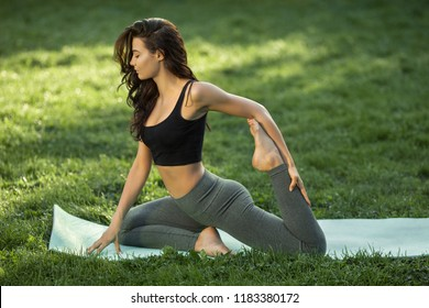 Woman practicing yoga performing yoga-asanas. Young attractive slim girl in bodysuit relaxing and doing exercises, sitting in variation of One Legged King Pigeon Posture on a yoga mat. Gorgeous