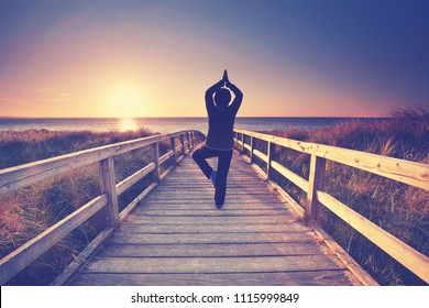 woman practicing yoga pose on the beach in summer. Healthy lifestyle and meditation.