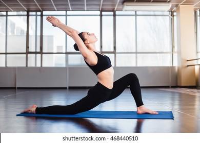 Woman practicing yoga pose Warrior in gymnastic studio
