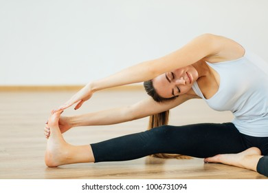 woman practicing yoga, sitting in Head to Knee Forward Bend exercise, Janu Sirsasana pose