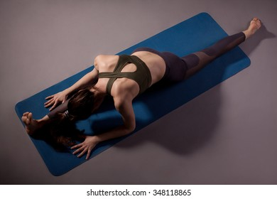 Woman practicing yoga in the splits position on the floor. Studio shoot