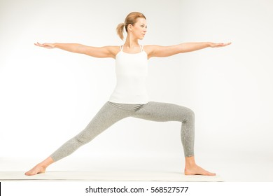 Woman practicing yoga standing in variation of Warrior 2 posture or Virabhadrasana Two pose isolated on white