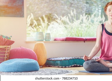 Woman practicing yoga in a studio with colorful cushions and beautiful window view