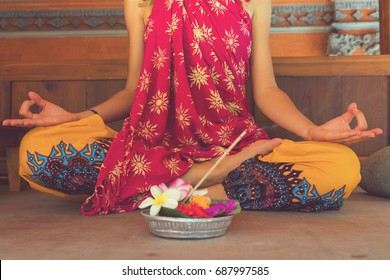 Woman practicing yoga in traditional Balinese house.
