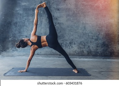 Woman practicing yoga in a urban background (side plank pose, vasisthasana)