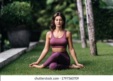 Woman practicing yoga-asanas outdoors. Young attractive slim fitness girl in bodysuit relaxing and doing exercises.
