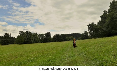 A woman with a pram on the field. Location: Europe, Czechia, near Horni plana