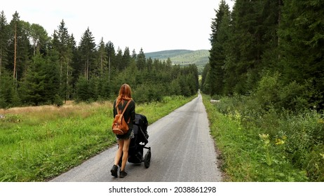 A woman with a pram on the road. Location: Europe, Czechia, near Horni plana