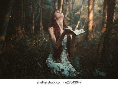 Woman praying alone in the forest. Dark and surreal