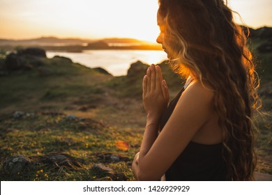 Woman praying alone at sunrise. Nature background. Spiritual and emotional concept. Sensitivity to nature