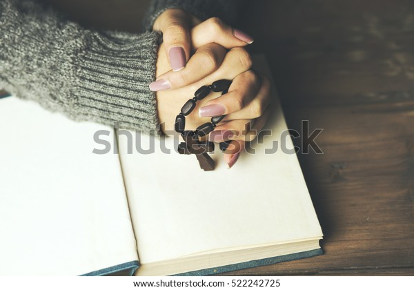 Woman praying with  bible and cross on table