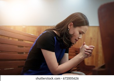 Woman praying in the church, Hands folded in prayer concept for faith, spirituality and religion