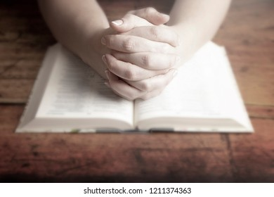 A Woman Praying with Her Hands Folded over Her Bible