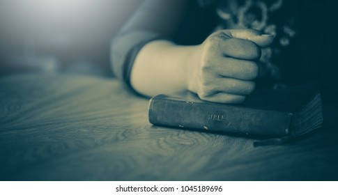 woman praying in the morning.Asian girl hand praying on holy bible in wooden table,Hands folded in prayer concept for faith,spirituality and religion.Vintage tone.