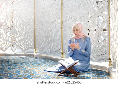 woman praying in the mosque and reading the Quran