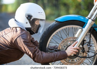 Woman praying to motorcycle, side view