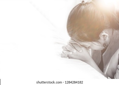 woman praying on the bed in the morning.Senior Adult woman hand with faith.Hands folded in prayer and focus to GOD at home concept for Salvation, Repentance, Pray, Faith, Spirituality and Religion.