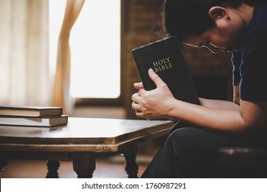 Frauen beten morgens auf heilige Bibel. Hände im Gebet auf einer Heiligen Bibel in der Kirche Konzept für Glauben, Spiritualität und Religion gefaltet