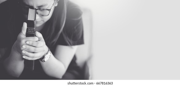 woman praying on holy bible in the morning.teenager woman hand with Bible praying,Hands folded in prayer on a Holy Bible in church concept for faith, spirituality and religion.