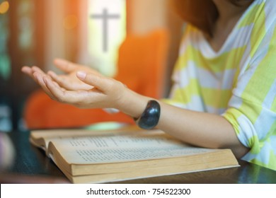woman praying on holy bible in the morning. teenager hand with Bible praying,Hands folded in prayer on a Holy Bible in church concept for faith, spirituality and religion. victory concept for god.
