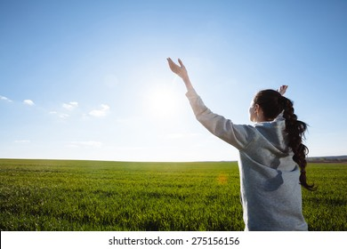 woman praying outside with hands raised