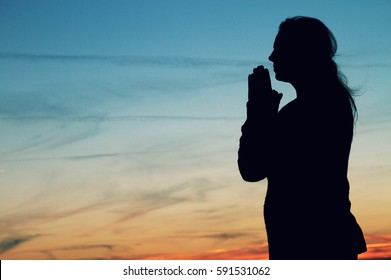 Woman praying silhouette at sunset